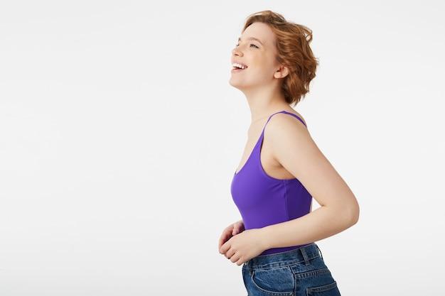 Портрет молодой привлекательной девушки с короткой стрижкой, одетой в фиолетовый свитер и джинсы, широко улыбающейся, позирующей в профиль, смеющейся смешными шутками, изолированной.