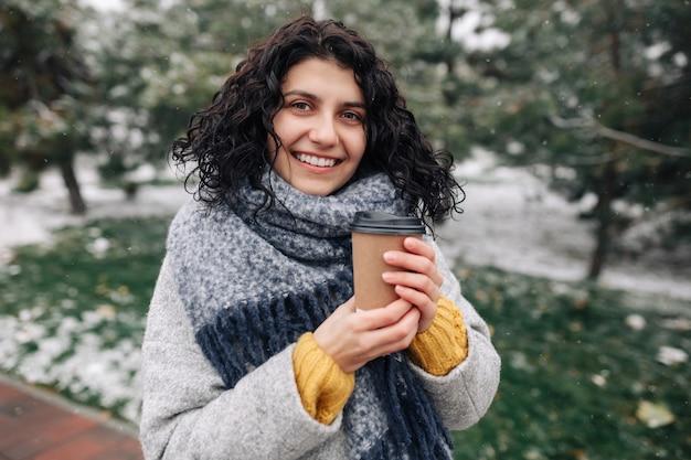雪に覆われた冬の公園でコーヒーを保持している若い魅力的な女性の肖像画。
