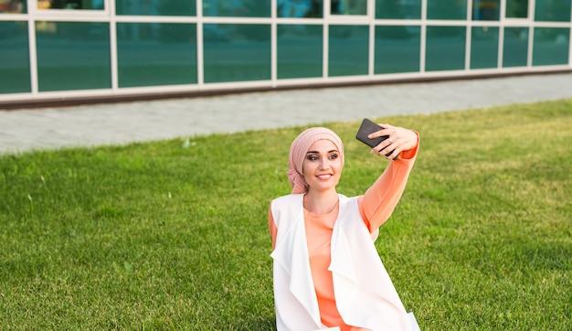 ヒジャーブの若い魅力的な女性の肖像画は公園でスマートフォンで自分撮り写真を作る