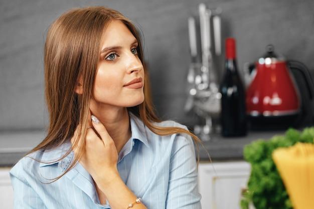 Портрет молодой привлекательной женщины на кухне крупным планом