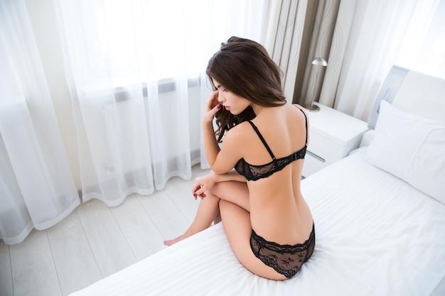Портрет молодой привлекательной женщины в нижнем белье, сидящей на кровати