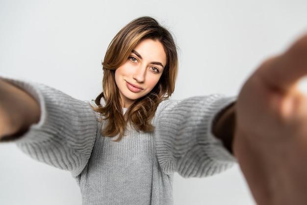 灰色の壁に分離されたスマートフォンでselfie写真を作る若い魅力的な女性の肖像画