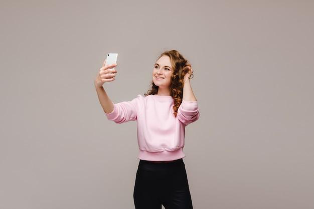 白い背景で隔離のスマートフォンでselfie写真を作る若い魅力的な女性の肖像画。