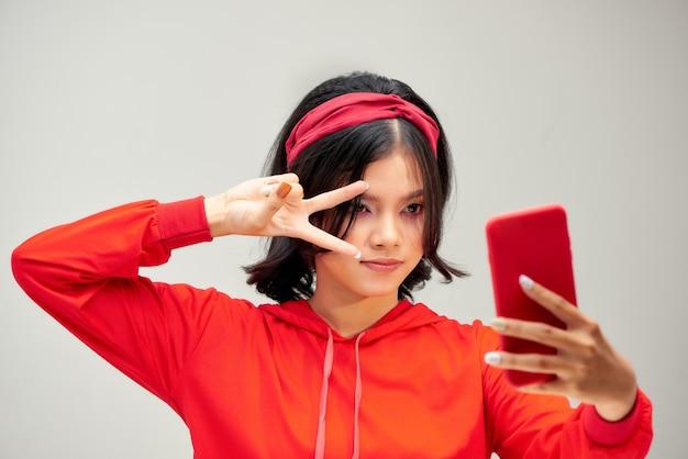 白い背景で隔離のスマートフォンでselfie写真を作る若い魅力的な女性の肖像画