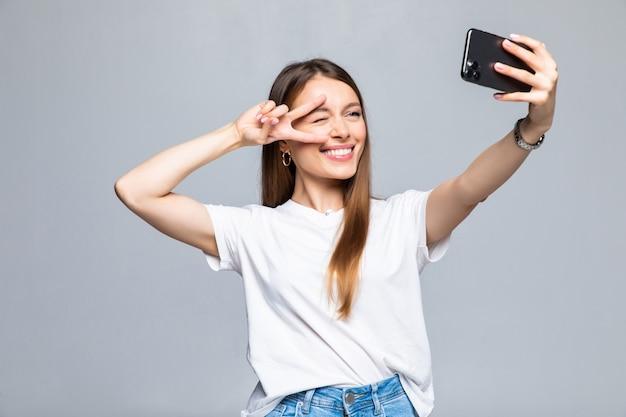 고립 된 스마트 폰에 selfie 사진을 만드는 젊은 매력적인 여자의 초상화