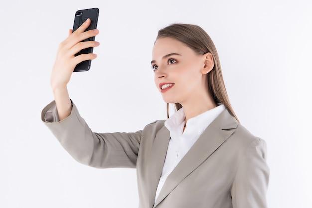 分離されたスマートフォンでselfie写真を作る若い魅力的な女性の肖像画