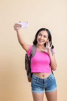 스마트 폰으로 셀카 사진을 만드는 젊은 매력적인 여자의 초상화
