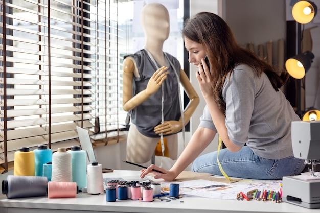 カラーテキスタイルのサンプルに囲まれた、スタイリッシュなファッションデザイナーのテーブルに座っている若い魅力的な女性の肖像画。マネキンとカラフルな布でファッションスタジオで働く魅力的な女性。