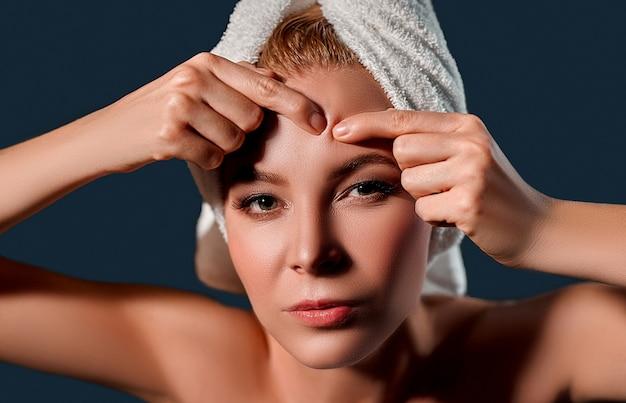 Портрет молодой привлекательной женщины с полотенцем на голове сжимает прыщи на черной стене.