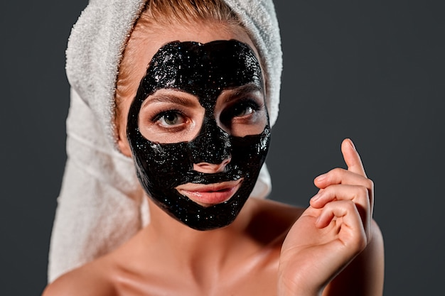 灰色の壁に彼女の顔にクレンジングブラックマスクを彼女の頭にタオルで魅力的な若い女性の肖像画。