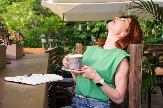 ジーンズの赤い髪と彼の手にコーヒーのカップを持つ緑の半袖ブラウスを持つ若い魅力的な女性の肖像画。女性は木の椅子にもたれかかった。朝のコーヒーをお楽しみください