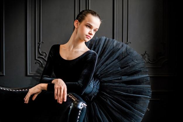 어두운 공간에 검은 투투를 입은 젊은 발레리나 소녀의 초상화 프리미엄 사진