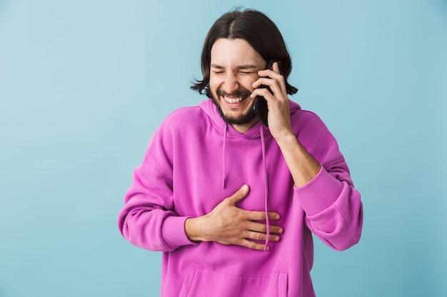 Портрет молодой бородатой брюнетки в толстовке с капюшоном, стоящей изолированно над синей стеной, разговаривает по мобильному телефону и смеется