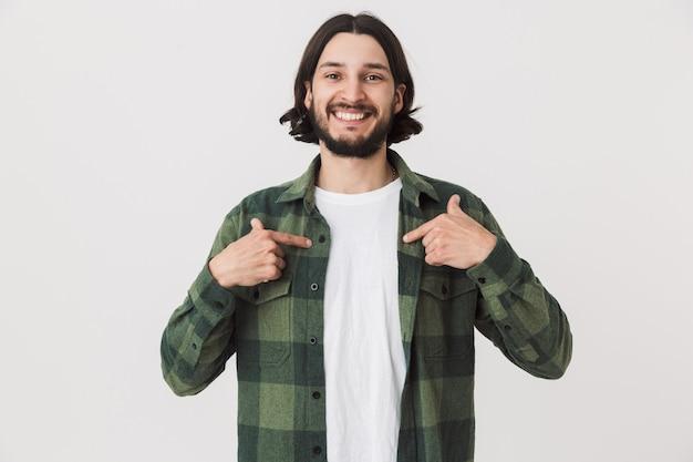 白い壁の上に孤立して立っている格子縞のシャツを着て、自分自身を指している若いひげを生やしたブルネットの男の肖像画