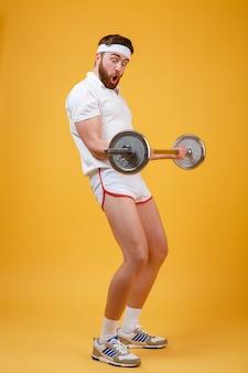 Портрет молодого бородатого мужчины фитнеса, делающего тренировку