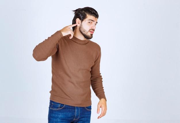 白い壁に隔離された指で耳を指している若いひげを生やした男の肖像画。高品質の写真
