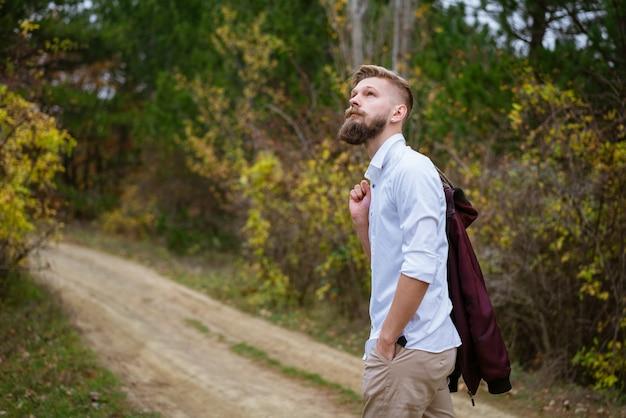 秋のハンサムな白人男性の公園の道路を歩いている若いひげを生やした男の肖像画