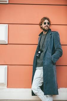 Портрет молодого бородатого мужчины с винтажной камерой