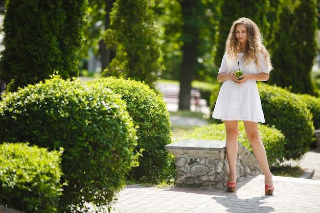 氷の冷たいジュースや飲み物のグラスと夏に屋外で若い美しい魅力的な女性の肖像画。新鮮なモヒートのフルハイトと外のきれいな女の子