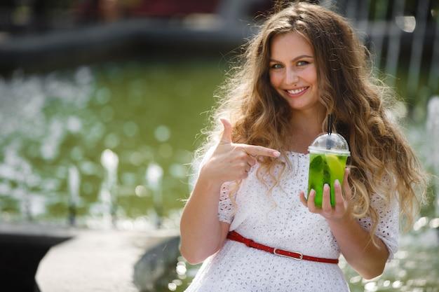 氷の冷たいジュースや飲み物のグラスと夏に屋外で若い美しい魅力的な女性の肖像画。新鮮なモヒートと外のきれいな女の子