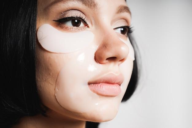 Портрет молодой красивой черноволосой женщины, она ухаживает за своей кожей, смотрит вправо