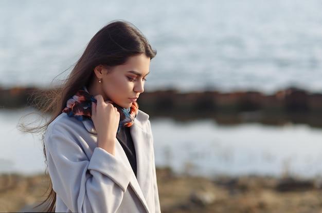 Портрет молодой красивой харизматичной брюнетки в пальто на берегу моря