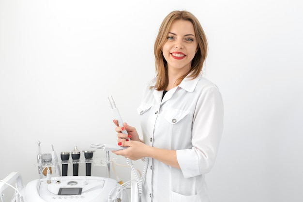 ノズルを保持している白いオフィスで白衣を着た若い美しい美容師の医者の女の子の肖像画