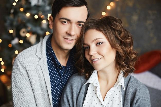 Портрет молодой красивой пары, влюбленной в праздничные рождественские огни