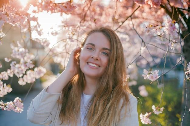 피 사쿠라 정원에서 젊은 아름 다운 곱슬 머리 여자의 초상화. 봄.