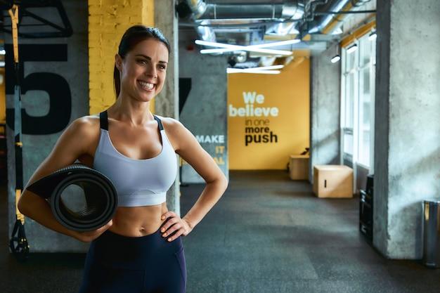 Портрет молодой красивой женщины фитнеса в спортивной одежде, держащей коврик для йоги и улыбающейся в камеру во время тренировки в тренажерном зале. спорт, хорошее самочувствие и здоровый образ жизни