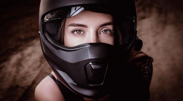검은 오토바이 헬멧에 젊은 아름 다운 여자의 초상화. 모터 스포츠 개념입니다. 혼합 매체