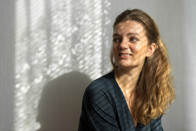Портрет молодой красивой девушки в комнате на фоне серой стены с тенями