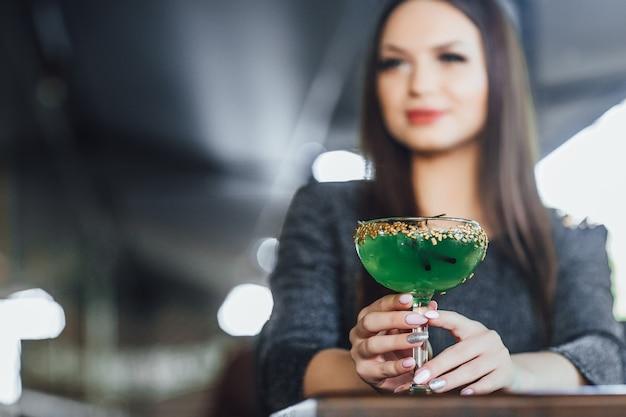 Портрет молодой красивой девушки на летней террасе современного кафе. она сидит и пьет зеленый коктейль.