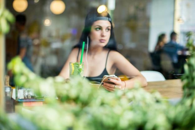 아름 다운 젊은 여자의 초상화입니다. 그녀는 카페에 혼자 앉아 헤드폰으로 음악을 듣습니다. 창을 통해 쐈 어.