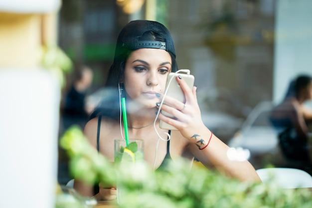 아름 다운 젊은 여자의 초상화입니다. 혼자 카페에 앉아 헤드폰으로 음악을 들으며 스마트폰 카메라로 화장을 확인한다. 창을 통해 쐈 어.