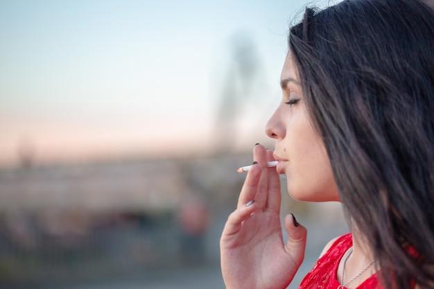 Портрет молодой красивой девушки, которая курит сигарету. портрет крупным планом.