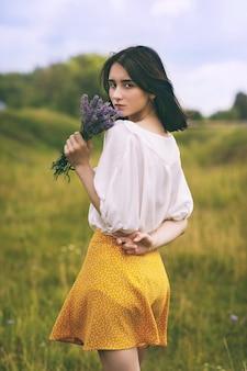ラベンダーの花束を持つ若い美しい少女の肖像画