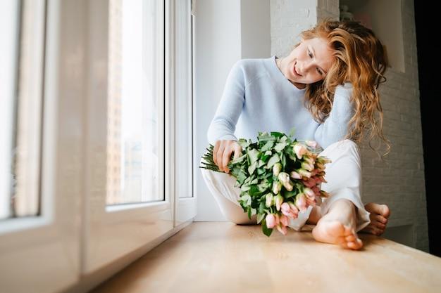 창 근처 장미 꽃다발과 함께 젊은 아름 다운 여자의 초상화. 곱슬거리는 붉은 머리.