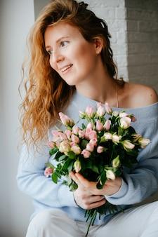 窓の近くにバラの花束を持つ若い美しい少女の肖像画。巻き毛が流れる赤い髪。