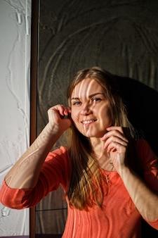 濡れた窓から光と若い美しい少女の肖像画。水と顔の光による汚れ