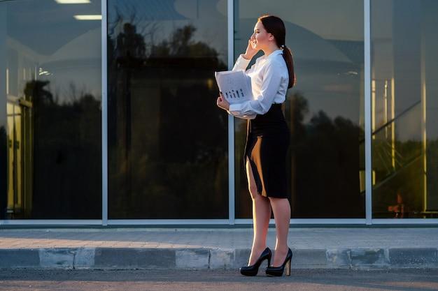 사무실 옷을 입은 젊은 인도 여성 사업가의 초상화와 완전히 성장한 서류, 사무실에서 전화 통화