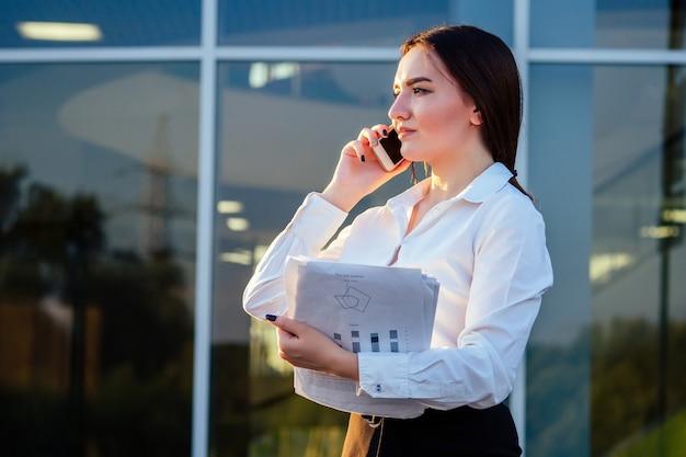 사무실 옷을 입고 사무실에서 전화 통화를 하는 서류를 입은 젊은 인도 여성 사업가의 초상화.