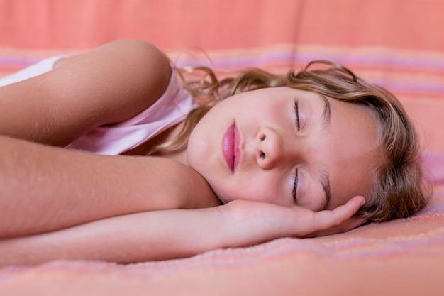 ベッドで休んだり、昼寝をしている若い美しい子供の肖像画。屋内での家族のライフスタイル。リラックスコンセプト