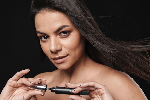 Портрет молодой красивой обнаженной женщины, позирующей изолированной над черной стеной, держащей тушь, наносит макияж.