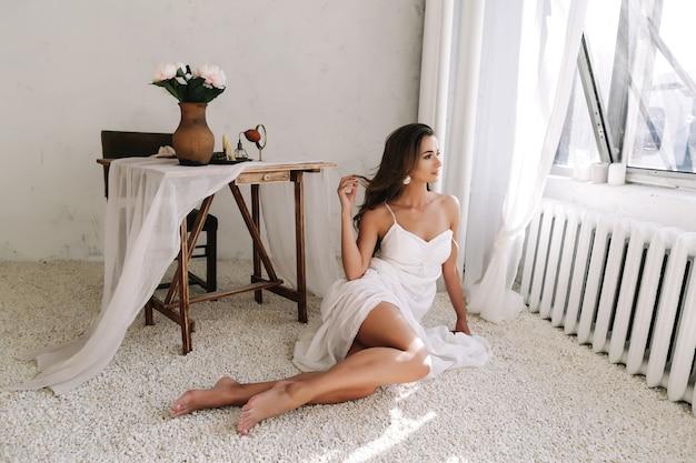 젊은 아름 다운 섹시 한 여자의 초상화입니다. 사실. 흰 드레스를 입은 긴 검은 머리를 가진 아름 다운 소녀