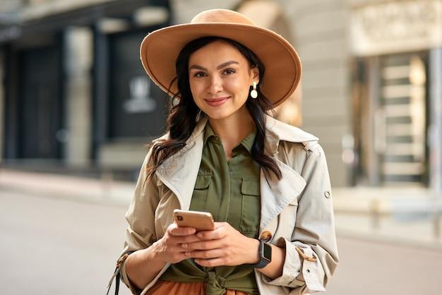 스마트폰을 들고 가을 코트와 모자를 쓴 젊고 세련된 여성의 초상화