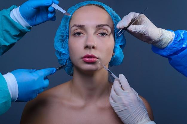 Портрет молодой красивой женщины в медицинской кепке рядом с четырьмя руками пластических хирургов, держащих хирургические инструменты