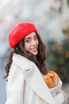 Портрет молодой красивой женщины в красном берете в европейском городе. молодая женщина держит бумажный пакет с багетами. рождество. каникулы.