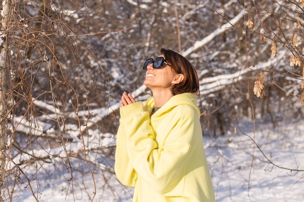 화창한 날에 눈 덮인 풍경 겨울 숲에서 젊은 아름 다운 여자의 초상화, 태양과 눈을 즐기는 선글라스와 함께 노란색 큰 풀오버를 입고