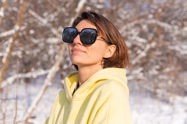 晴れた日の雪景色の冬の森で、サングラスをかけ、太陽と雪を楽しんで、黄色の大きなプルオーバーに身を包んだ若い美しい女性の肖像画